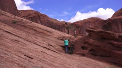 Outside ARCHES NATIONAL PARK, woman climbing ladder Stock Footage