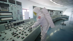 4K Astronaut alone in mission control room, pressing switches on control panel Stock Footage