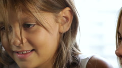 closeup of two young girls talking and looking at something - stock footage