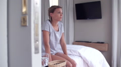 Woman sitting on edge of bed, looking down - stock footage