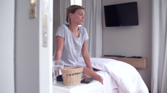 Woman sitting on edge of bed with unhappy expression Stock Footage
