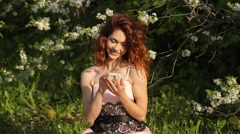 Girl with red hair uses a smartphone Stock Footage