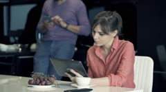 Couple at home, woman using tablet, man typing on smartphone in the background Stock Footage