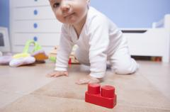 baby boy playing with plastic building blocks - stock photo