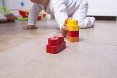 Baby boy playing with plastic building blocks Stock Photos