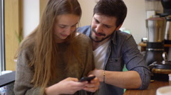 Affectionate couple looking at smartphone together in coffee shop Stock Footage