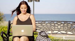 Attractive woman typing on her laptop outdoors Stock Footage