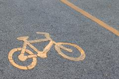Bicycle lane signage on street. Yellow bicycle sign on asphalt bike lane. Stock Photos