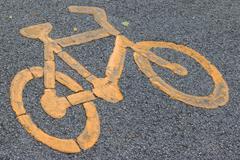 Bicycle lane signage on street. Yellow bicycle sign on asphalt bike lane. - stock photo