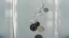 Coins Fall into Water Glass of Water - stock footage