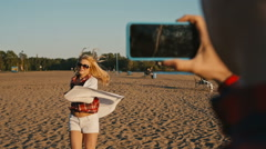 Beautiful girl dancing on the beach her boyfriend shooting this on phone Stock Footage