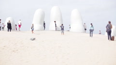 Tourists photographing sculpture on beach at Punta del Este Stock Footage