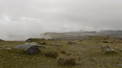 Time lapse of low clouds moving over rocky landscape Stock Footage