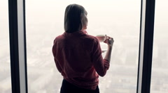 Young woman drinking coffee and admire view from window at home Stock Footage