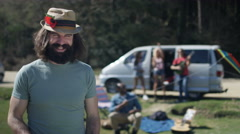 4K Portrait of smiling hipster guy with friends at music festival campsite - stock footage