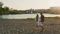 Yong couple walking on the beach Stock Footage