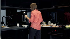 Young woman preparing breakfast, boiling water in electric kettle in kitchen Stock Footage