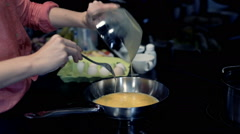 Woman preparing scrambled eggs on pan in kitchen at home Stock Footage