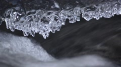 Stream of water flowing beneath the ice crust formed over water Stock Footage