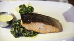 Preparing grilled salmon steak served with stirred spinach - stock footage