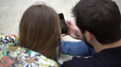 Couple looking at smartphone together, over the shoulder view Stock Footage