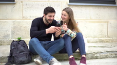 Couple sitting together on sidewalk, looking at smartphone Stock Footage