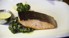 Preparing grilled salmon steak served with stirred spinach Stock Footage