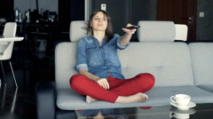Young, happy woman watching TV sitting on sofa at home Stock Footage