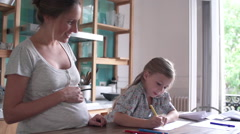 Expectant mother watching as her young daughter practices writing Stock Footage