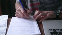Close-up of man writing in notebook with laptop computer nearby Stock Footage