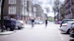 Cyclist riding bike down city street Stock Footage