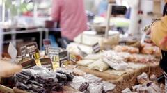 Customer sampling dried fruit at market stall Stock Footage