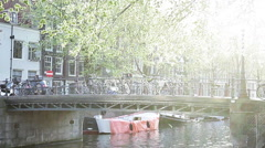 Riding bicycle across canal bridge in Amsterdam, Netherlands - stock footage