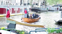 Motorboat with several passengers moving along canal in Amsterdam, Netherlands Stock Footage