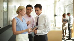 Business associates using digital tablet to collaborate on project - stock footage