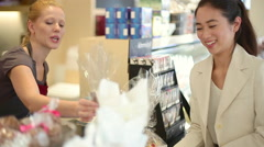 Cashier assisting customer at checkout counter in shop Stock Footage