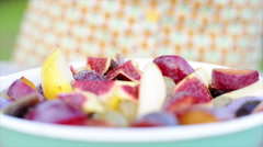 Woman shaking seasoning over cut-up fruits Stock Footage