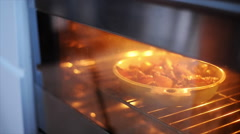 Woman taking baked fruit dish out of oven - stock footage