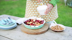 Woman putting creme and chopped nuts on fruit dessert Stock Footage
