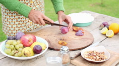 Woman cutting plum outdoors Stock Footage