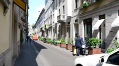 Shopping in Milan, Monte Napoleone, pedestrian and cars on the narrow street Stock Footage