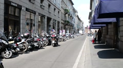 Shopping in Milan, Monte Napoleone, pedestrian and scooters on the narrow street Stock Footage