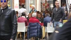 Senior age people sit drink at table street restaurant on crowd street Milan  Stock Footage