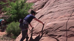 Ground crew holds rope, Moab, Utah rock climber Stock Footage