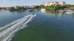 Aerial fly by Charter Boat as Jet Ski zooms by Along Vacation Tourist Shoreline Stock Footage