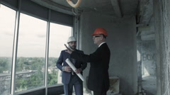 Two men in suit and helmet discuss blueprint, calculate and communicate with Stock Footage