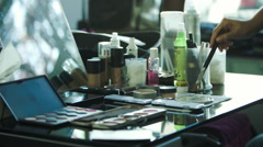 Woman reaching for variety of cosmetics products on table Stock Footage