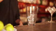 Bartender preparing cocktail by first squeezing fresh lime over ice Stock Footage