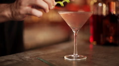 Bartender placing twist of lime rind on rim of martini glass - stock footage