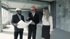 Men, woman in suit and helmet discuss blueprint, communicate with buyer. Chief Stock Footage